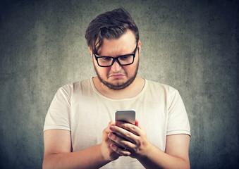 Upset man watching at smartphone