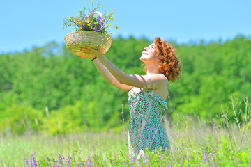 Girl is pleased with the gifts of summer and raises a bouquet of flowers to the sky
