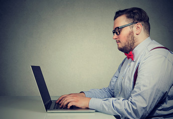 Obese man working at laptop in office