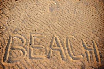 the word beach is written in the sand