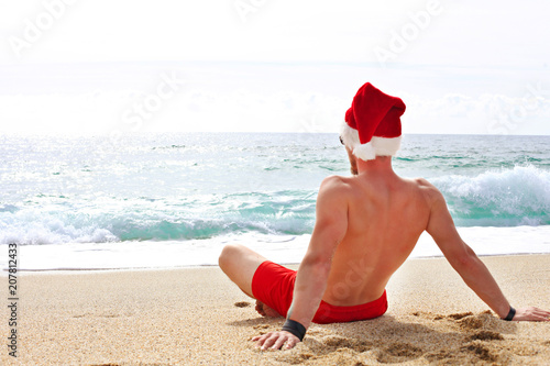 Christmas In July Background Images.Rear View Of Fit Young Man In A Santa Hat Celebrating