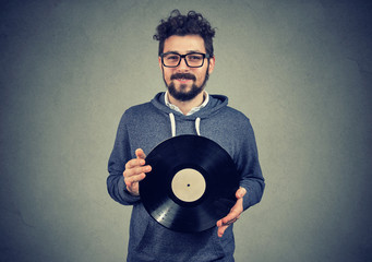 Happy hipster man with vinyl disk