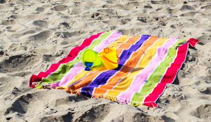 2 child's plastic sand pails and shovels with a colorful striped beach towel on a sandy beach
