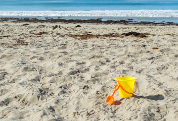 yellow child's plastic sand pail with orange shovel on a sunny summer day at the beach with the Pacific ocean in the distance