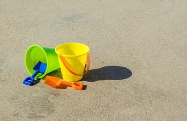 yellow and green child's plastic sand pails with orange and blue shovels at a sandy beach on a sunny summer day