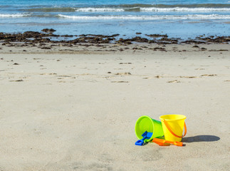 2 colorful plastic sand pails with shovels on a sunny summer day at the beach with the ocean in the distance