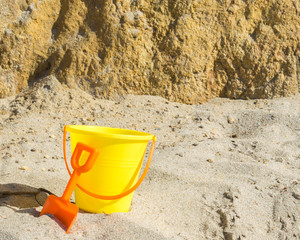 child's plastic yellow sand pail and orange shovel in the sand near a steep rocky wall on a sunny summer day