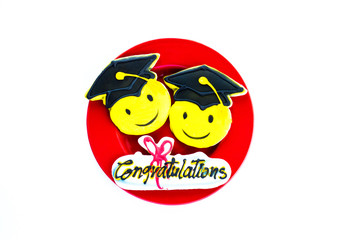 3 colorfully decorated graduation cookies on a red plate isolated on white