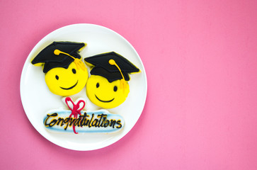 3 colorfully decorated graduation cookies on a white plate against a pink background with copy space