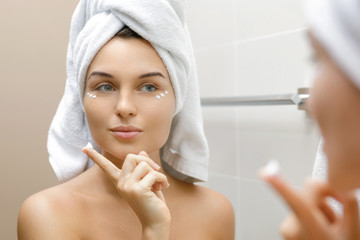 Woman using moisturizing and anti-aging cream under her eyes