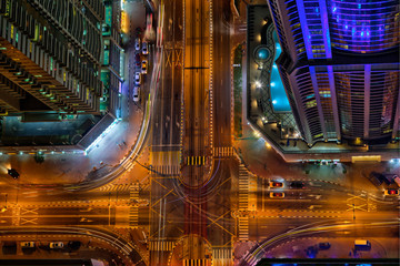 Top view on Dubai skyline during night with amazing city center crossroad lights and road traffic,United Arab Emirates.