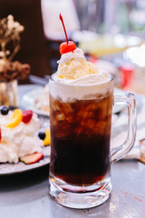 Sweet refreshing Cherry Cola topping with a scoop of vanilla ice cream and fresh cherry.