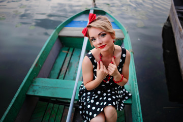 Beautiful young woman dressed dressed in a boat on a lake shore
