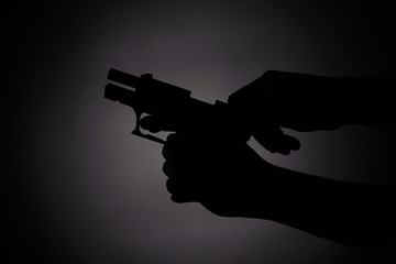 black silhouette of a male reloading a gun in the dark