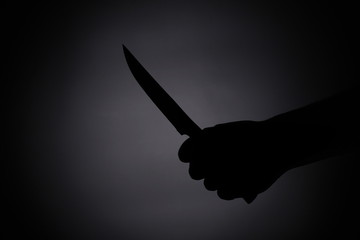 attacking with a knife / melee weapon shadow black silhouette in the dark