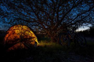 Illuminated camping tent and bicycles at night