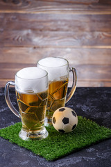 Photo of two beer mugs, green grass with soccer ball