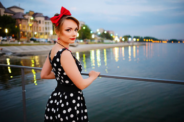 A beautiful young woman dressed stand on the pier in the evening