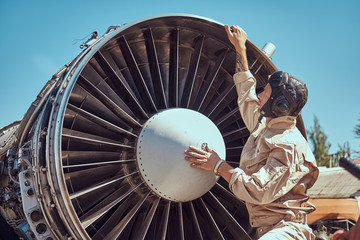Mechanic in uniform and flying helmet repairing the dismantled airplane turbine in an open-air museum.