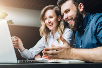 Teamwork. Businesswoman and businessman are sitting at desk against laptop and discussing business project, working together. Woman and man happily look at laptop screen. Business meeting, marketing.