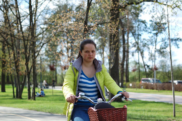 A girl is riding a bicycle in the park.