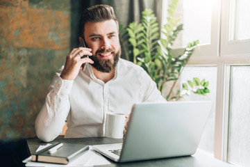 Young smiling bearded businessman is sitting at table in front of laptop, drinking coffee, talking on cell phone. Telephone conversations, distance work, online marketing, education, e-commerce.