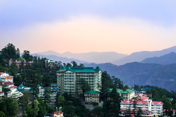Buildings of shimla shot against the blue and pink dusk sky in Shimla. The hills and mountains fading off into the distance shows the beauty of the place
