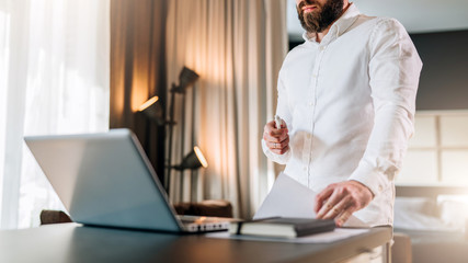 Young bearded businessman in white shirt is standing near desk in front of laptop, holding documents. Freelancer working home. Student learning online. Online marketing, education, e-learning.