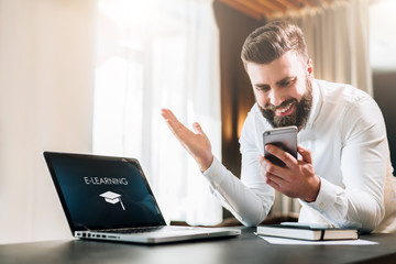 Young bearded businessman in a white shirt is sitting at a table in front of a laptop with an inscription e-learning on screen and is happily looking at screen of smartphone, raising his hands up.