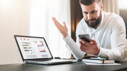 Young bearded businessman in a white shirt is sitting at a table in front of a laptop with graphs, charts, diagrams on screen and is happily looking at screen of smartphone, raising his hands up.