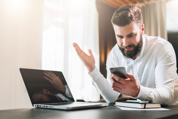Young bearded businessman in white shirt is sitting at table in front of laptop and is happily looking at screen of smartphone, raising his hands up.Online marketing, education, e-learning,e-commerce.