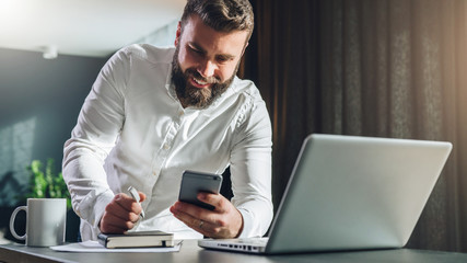 Young smilling bearded businessman standing near table in front of laptop, using smartphone. Man checks e-mail, chatting, blogging. Online marketing, education, social network, e-learning, e-commerce.