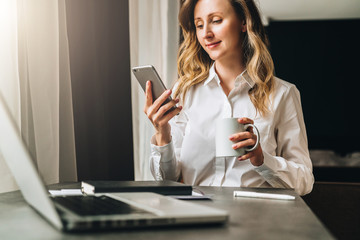 Young businesswoman in shirt is sitting in office at table in front of computer, using smartphone, looks at phone screen, holds cup of coffee in her hand. Social network, breaking. Student learning.