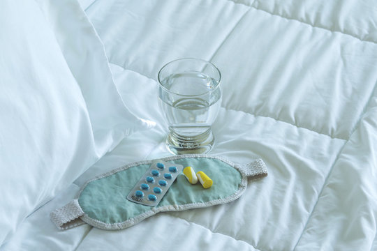 Blister pack of sleeping pills, blindfold and glass of water
