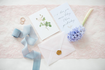 wedding invitation card as a decorated letter with flowers and ribbons top view