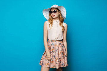 Beautiful and fashionable blonde model girl in beige blouse, pink skirt, stylish sunglasses and hat posing in studio at blue background