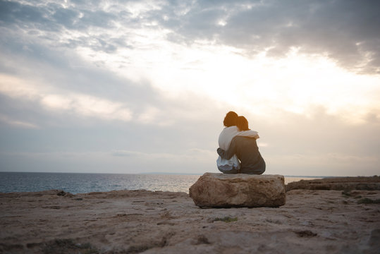 Full length back view of two pleasant women are sitting on the beach on big stone and having strong hug. They are looking at ocean while enjoying sundown. Copy space in the left side