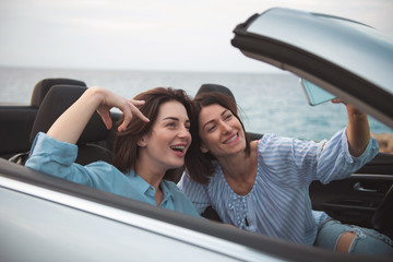 Best memories. Positive young happy women are taking selfie using smartphone while sitting in luxury car with open roof. They are smiling at camera while travelling along seashore. Vacation concept