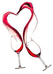 Wineglasses with red wine and heart shaped splash, isolated on white