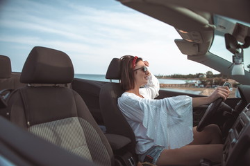 Love driving. Side view profile of happy delighted young woman is sitting in cabriolet while enjoying trip on luxury modern car with open roof. She is resting abroad. Fashionable lifestyle concept