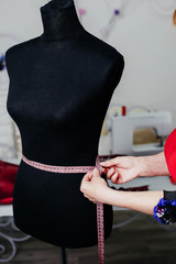 A woman seamstress is trying on fitting. Black mannequin. centimeter for sewing. Measures the shape