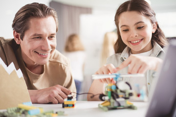 Portrait of beaming man and happy child creating toy while locating in classroom