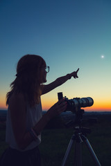 Young woman holding astronomical telescope and looking at the sky.