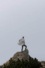 Young adult man in white coat standing on top of a mountain and in front of a wall of fog