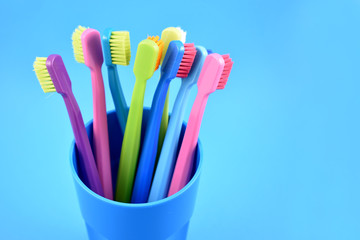 Colored toothbrushes stock images. Morning hygiene. Bathroom accessories images. Toothbrush on a blue background. Toothbrush on a blue background with copy space for text