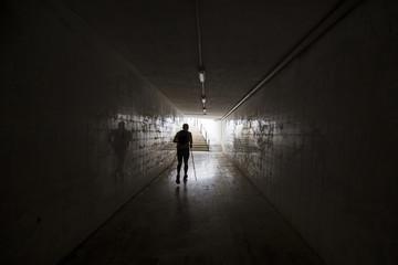 A runner' silhoutte on the dark tunnel runs to light