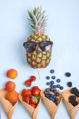 Pineapple and other berries and fruits on a blue background. Free space for text. Flat lay. Copy space,