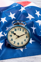 Flag of USA and blue alarm clock. Patriotic american flag and retro alarm clock, vertical image. Time to vote.