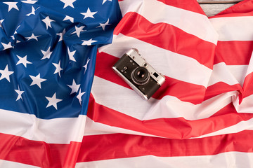 Vintage camera on national flag of America. Old film camera on USA flag. Stars and stripes flag.