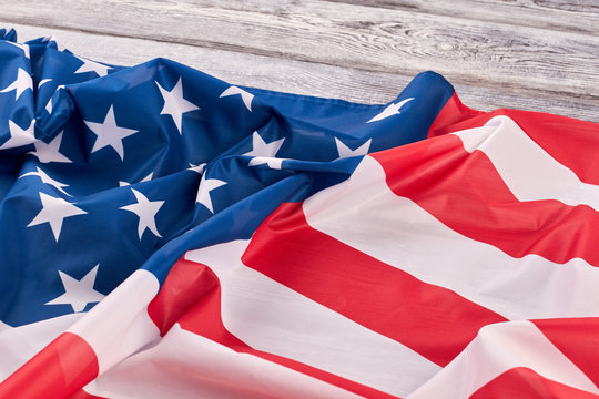 Crumpled flag of USA on wooden background. Patriotic flag of America on vintage wooden surface.